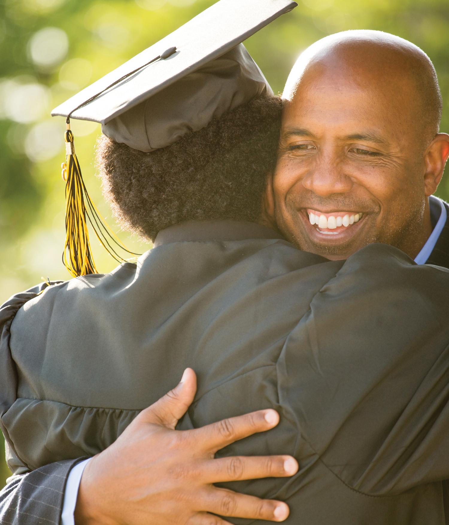 Dad hugging son in graduation cap